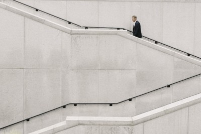 A man in a suit walks up an angular stairwell
